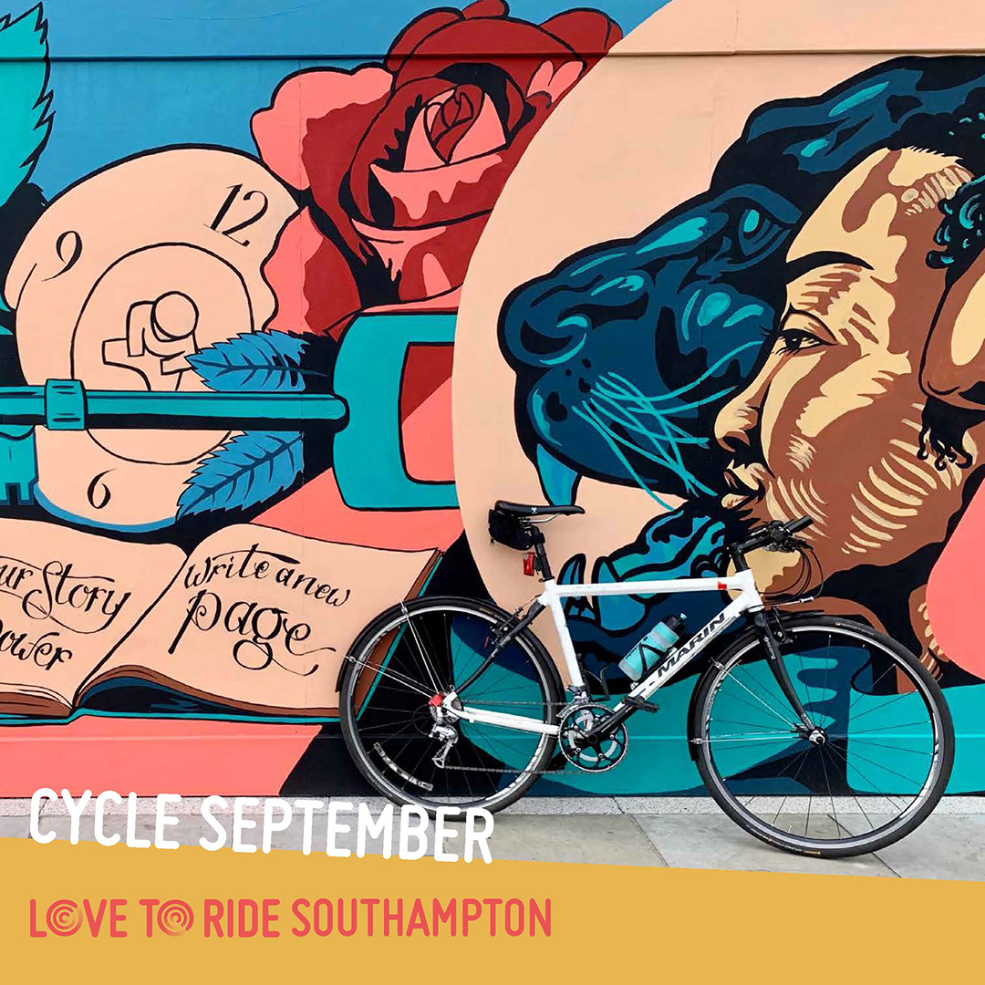 A bike propped up against a wall covered in a large colourful mural which contains images of faces, a key, and an open book containing the words 'your story your power, write a new page'.