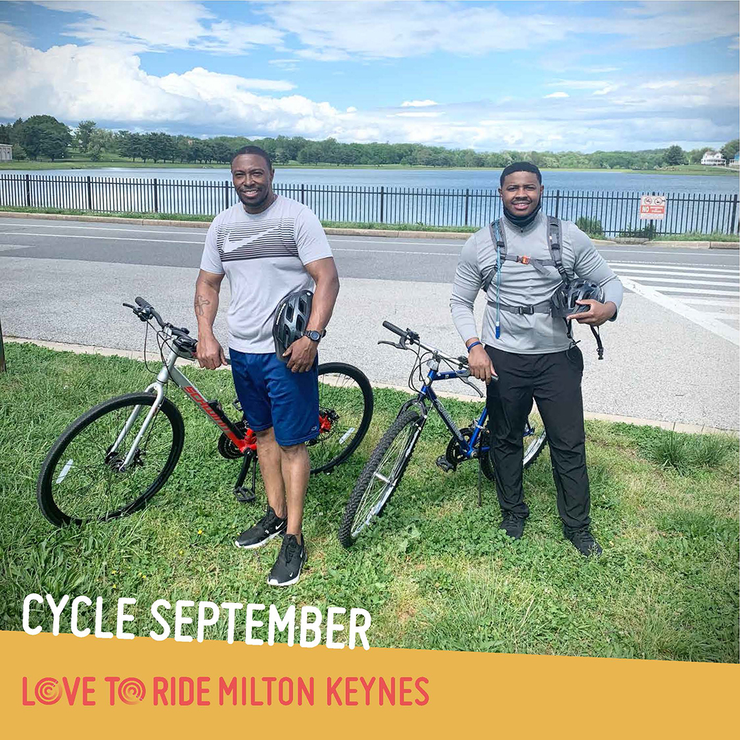 Two men stand with bikes on a grass verge next to a road and in front of a lake. They both hold helmets and are smiling. The text says 'Cycle September' and the Love to Ride logo is displayed.