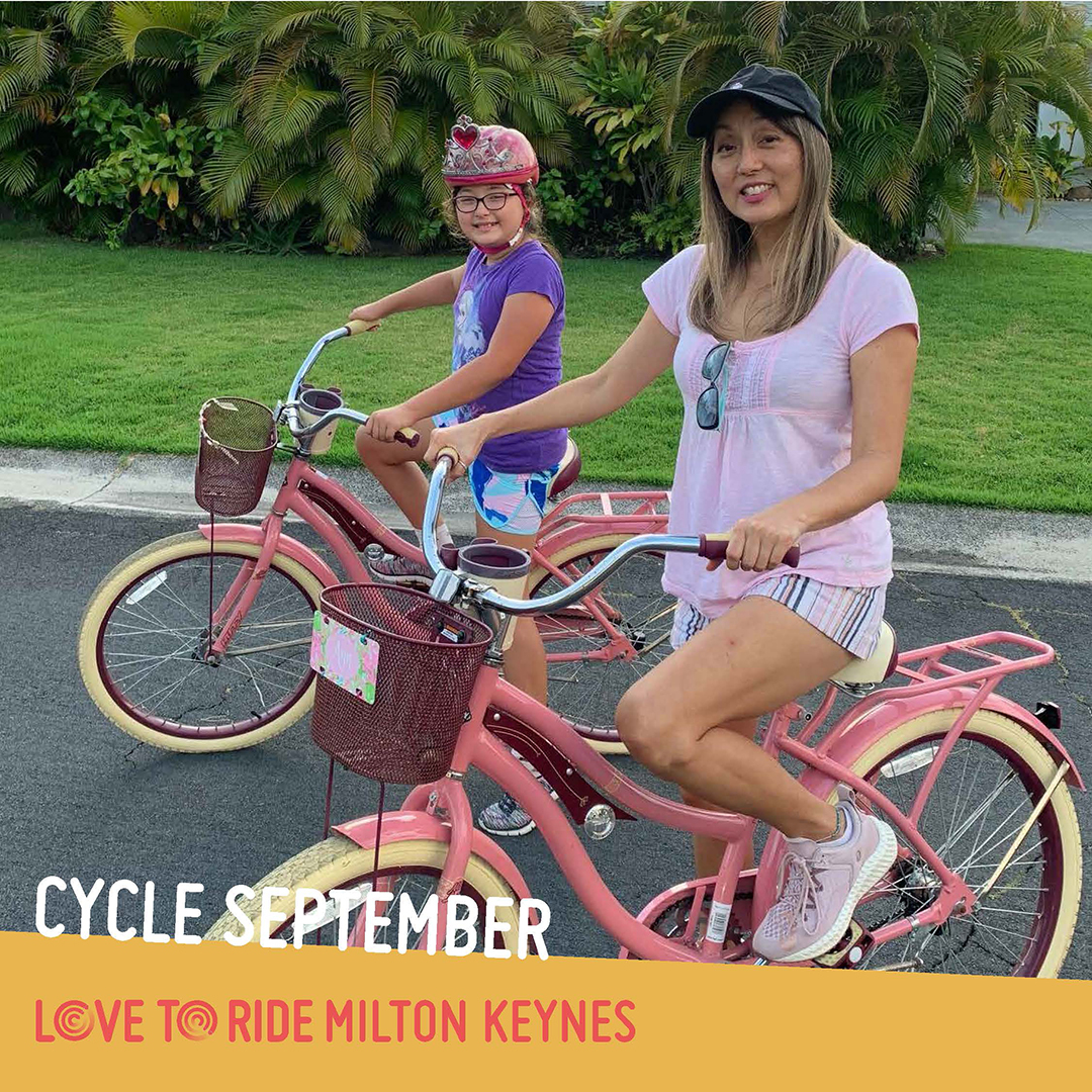 A woman and a girl pose on their matching pink shopper bikes and smile at the camera. The text says 'Cycle September' and the Love to Ride logo is displayed.
