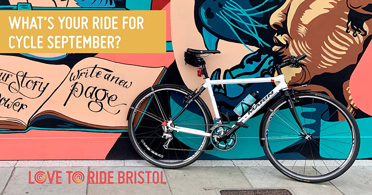 """A bike propped up against a wall covered in a large colourful mural which contains images of faces, a key, and an open book containing the words 'your story your power, write a new page'. The text says """"What's your ride for Cycle September?"""""""