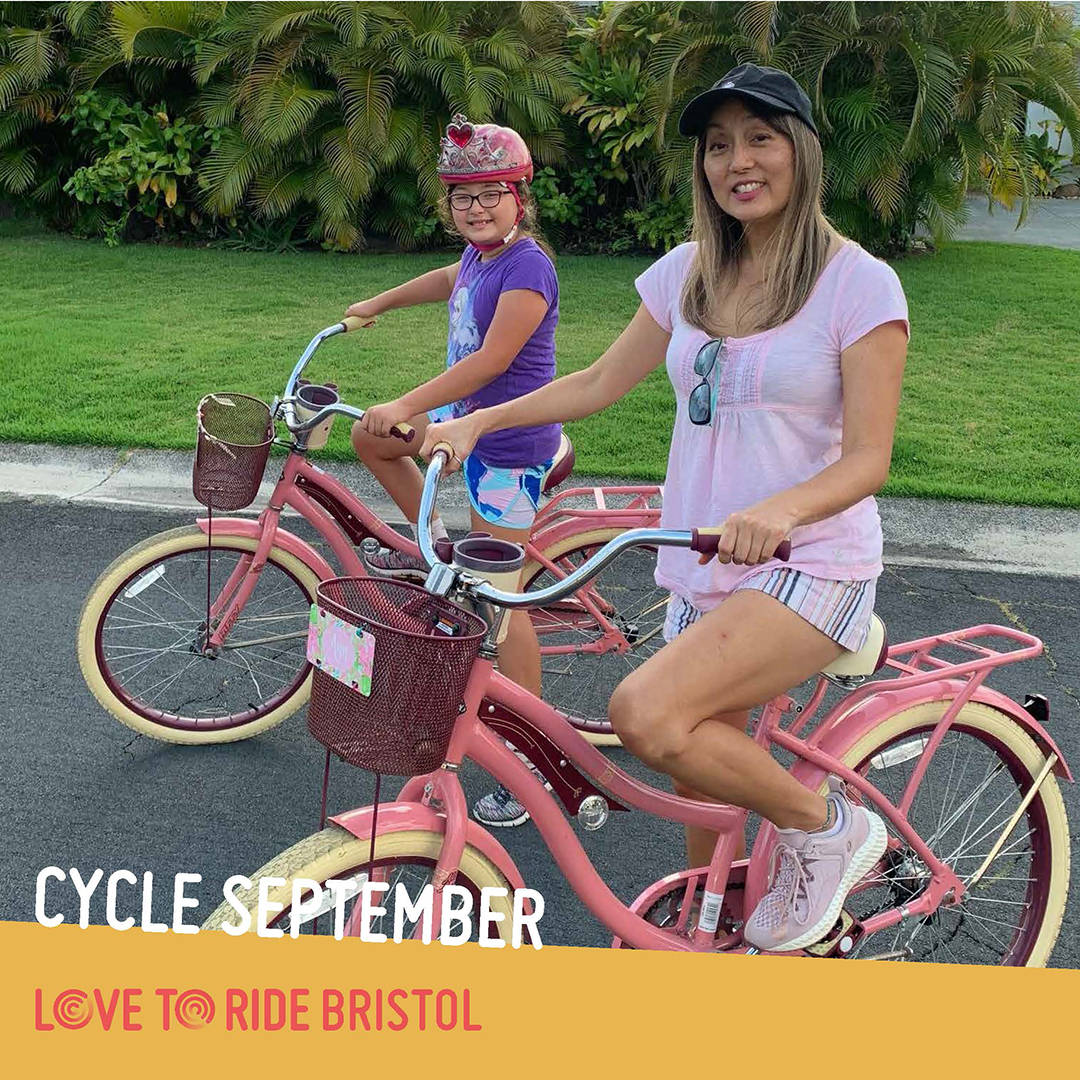 A woman and a girl (they appear to be mother and daughter) pose on their matching pink shopper bikes and smile at the camera. The text says 'Cycle September' and the Love to Ride logo is displayed.