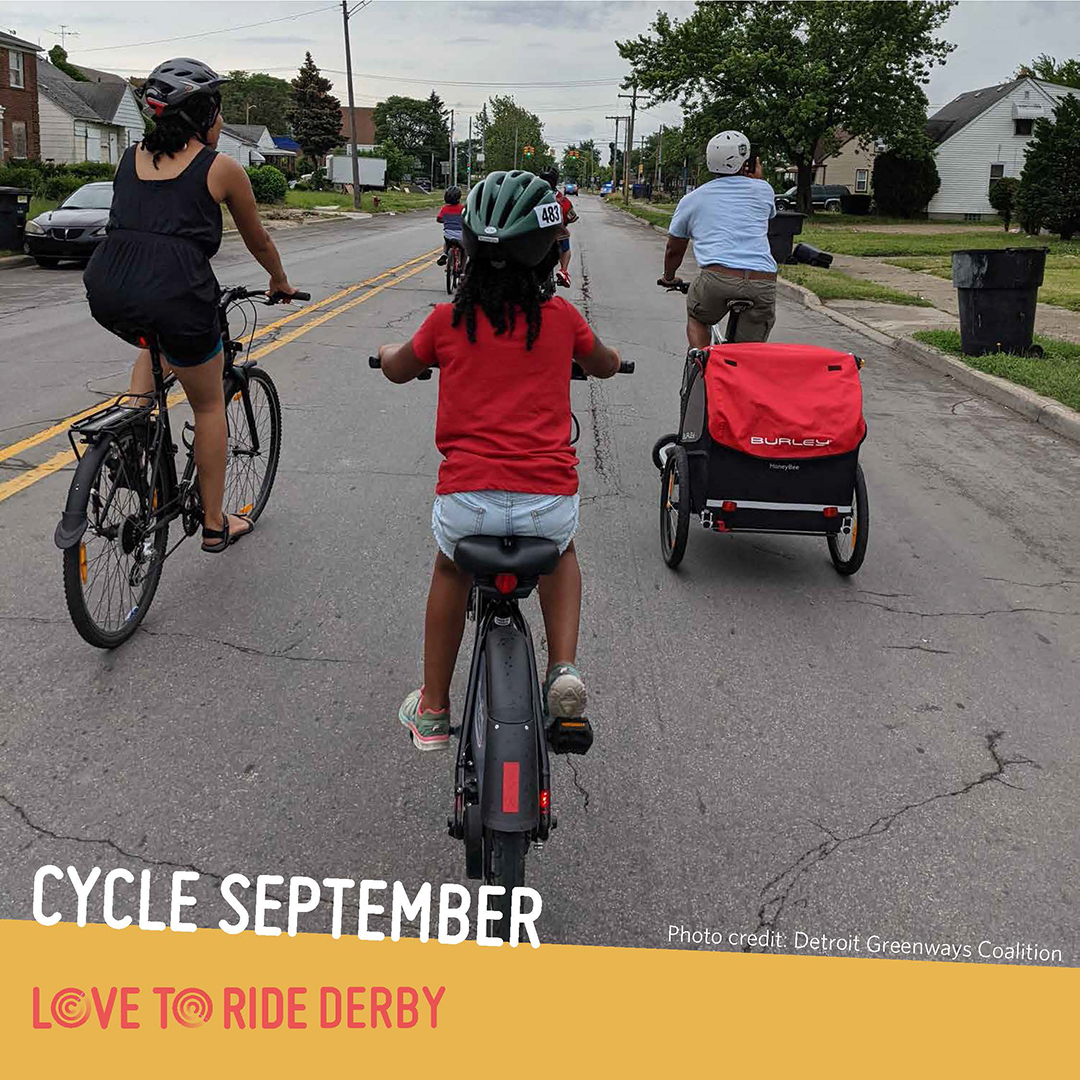 A family riding on a residential road, shown from behind. One person carries a trailer on their bike. The text says 'Cycle September. Photo credit: Detroit Greenways Coalition' and the Love to Ride logo is displayed.