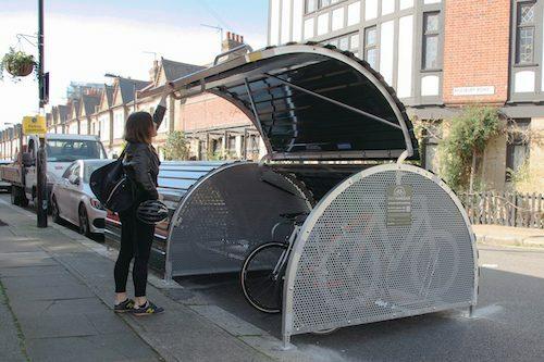 A bike locker being shut by a woman on a street