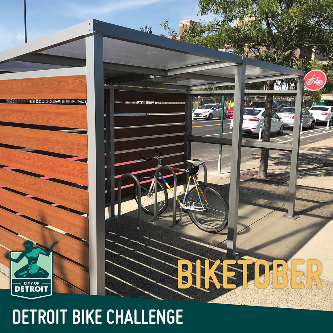 "A rainbow colored bike sits under a shaded bike rack. The text says ""Detroit Bike Challenge - Biketober"""