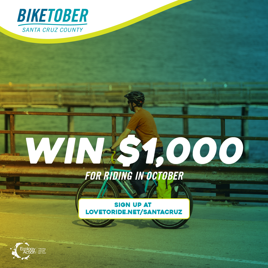 Biketober Santa Cruz County social media post with a person riding a bike down a coastal path. The ocean is on the right side to them. The rider has a helmet on and the image has a green blue overlay theme. Text reads 'win $1000 for riding in October'.