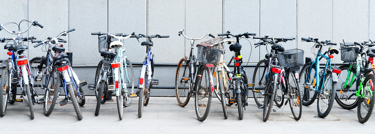 A row of bikes parked in front of a grey wall